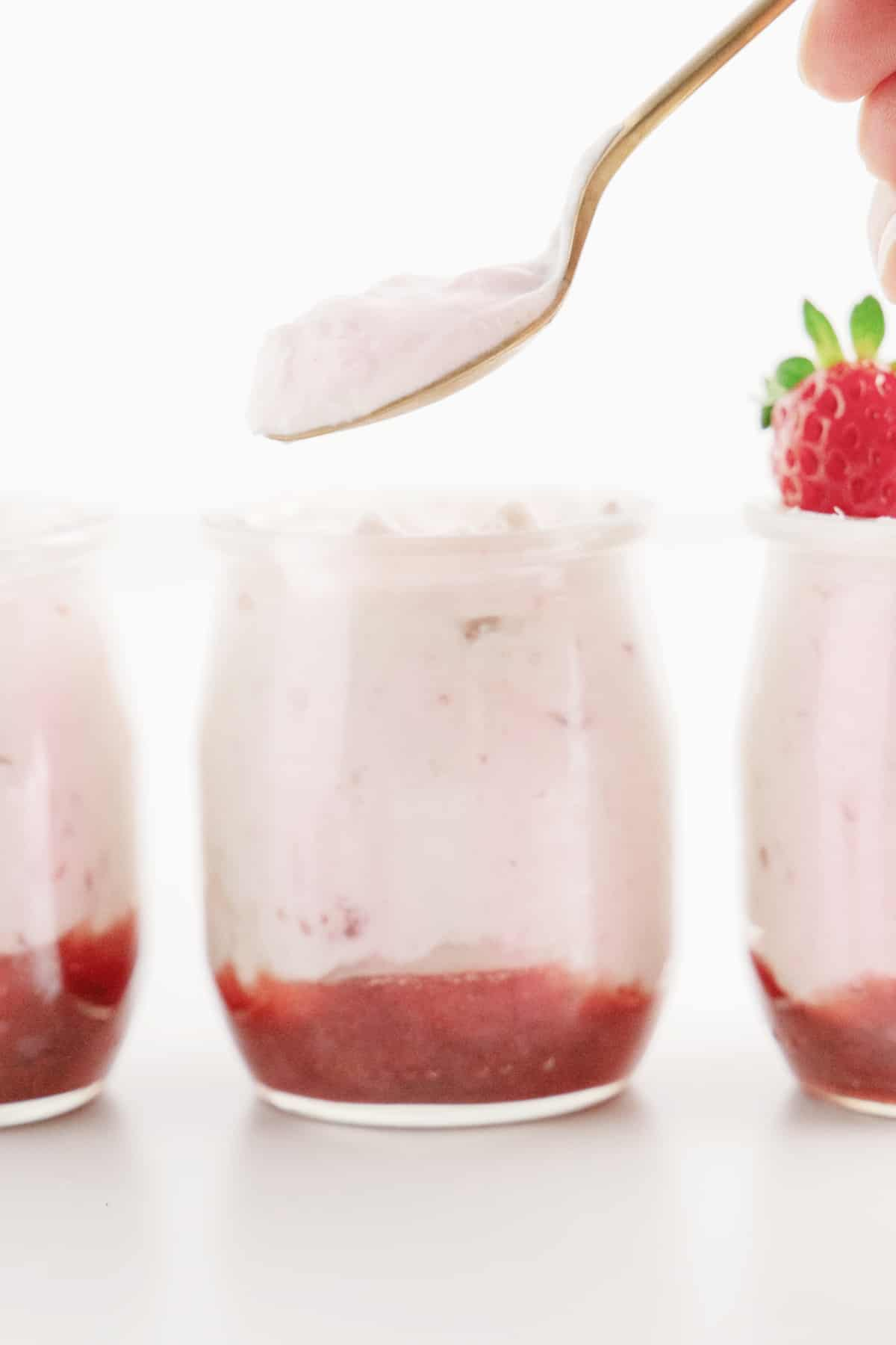 Three jars in a row, spooning mousse out of middle jar.