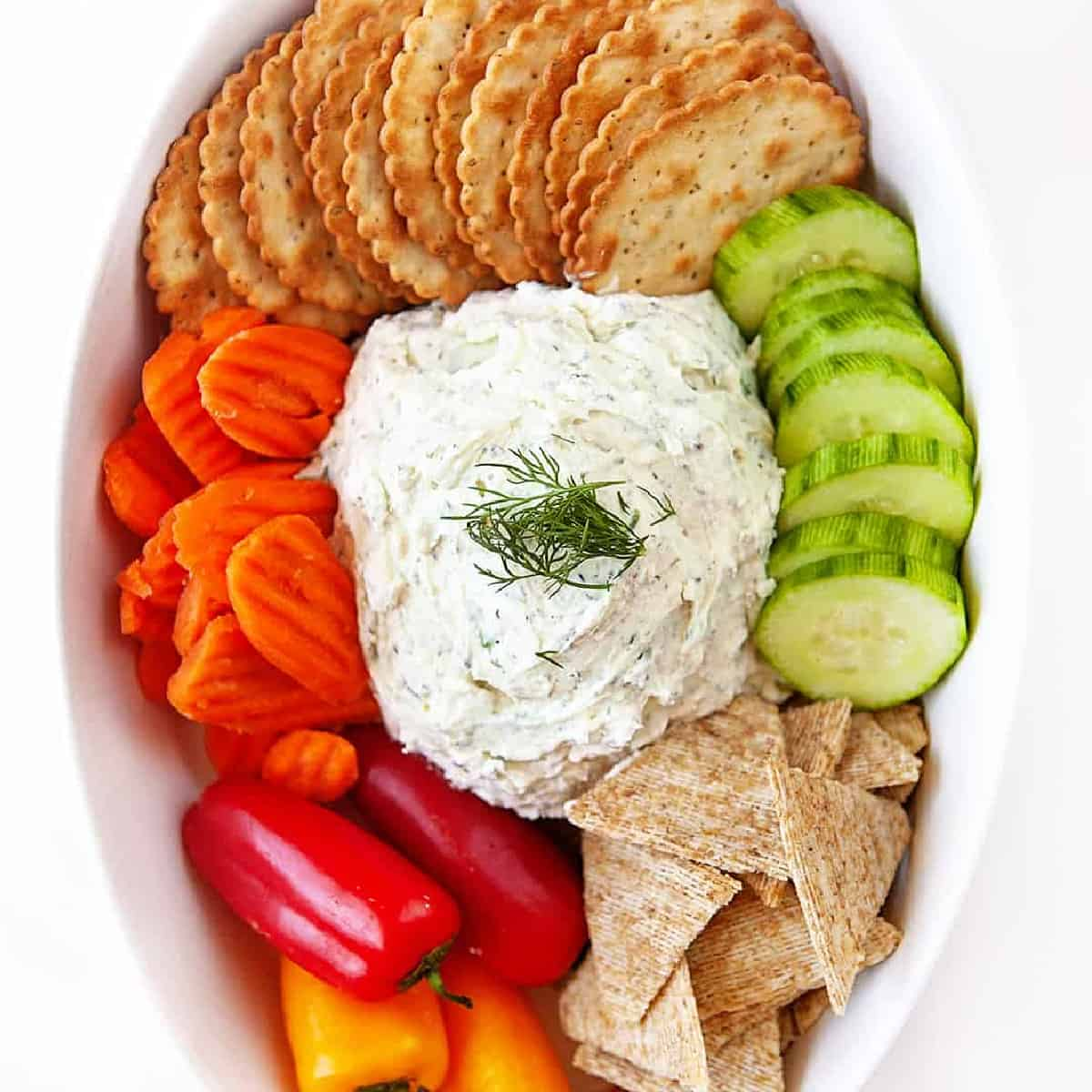 Overhead square photo of homemade boursin with veggies and crackers in a small white casserole dish.