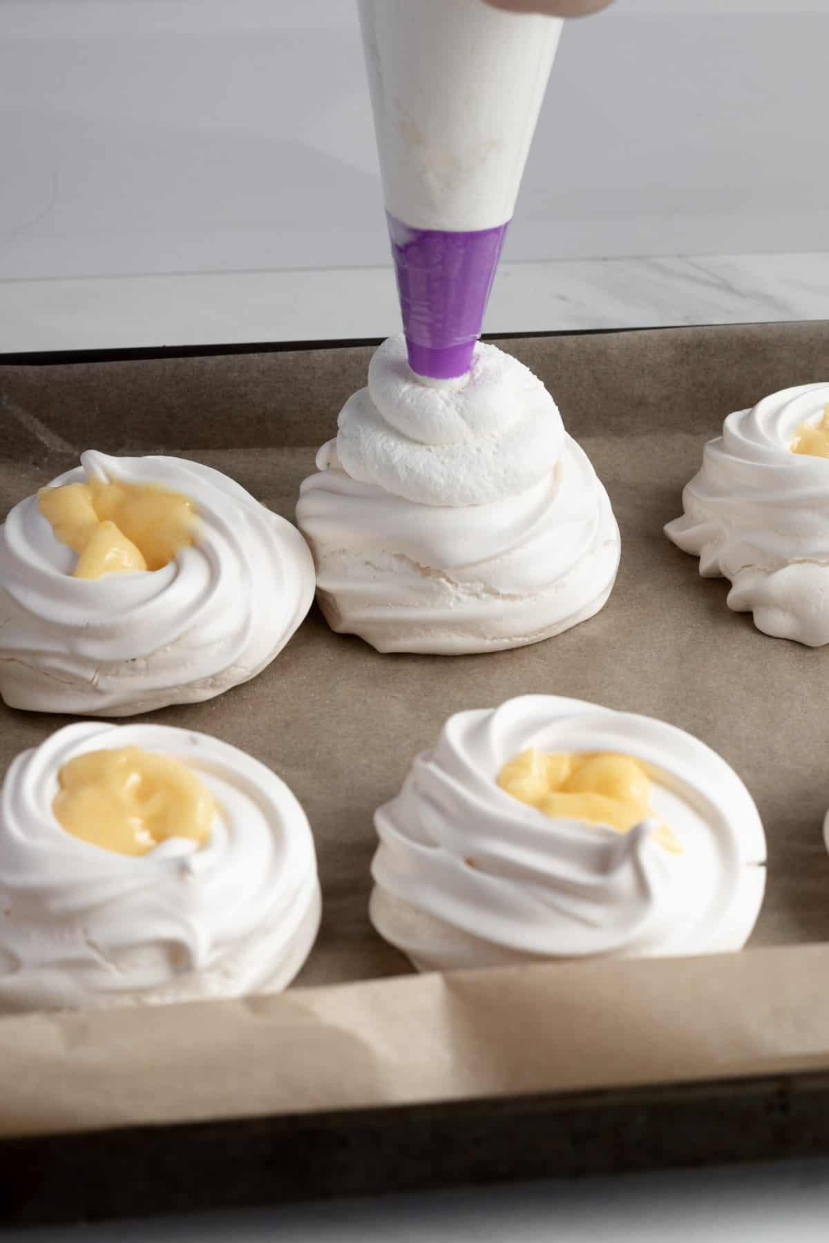 Piping whipped cream on top of a lemon curd filled pavlova