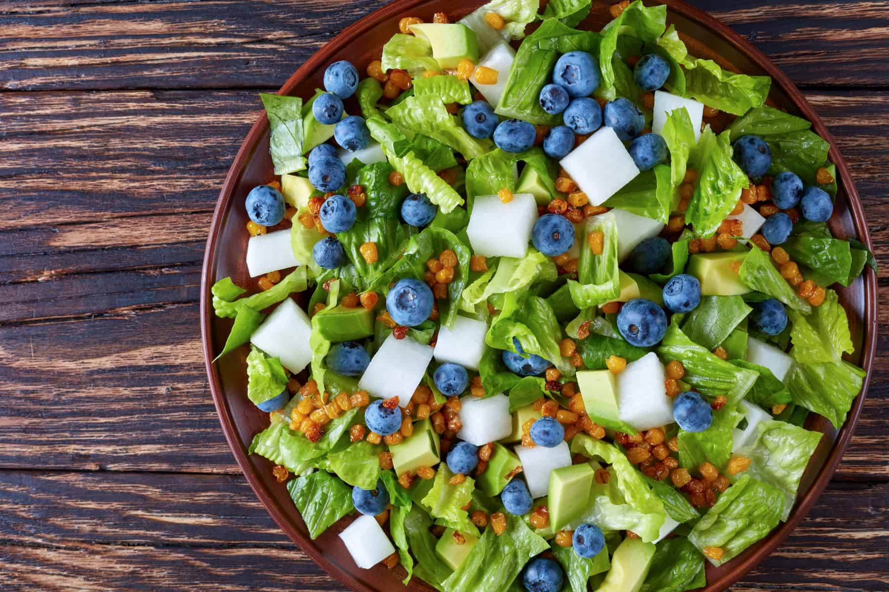 Mexican Salad with Blueberries, romaine lettuce leaves, jicama, roasted Corn kernels and Avocado on a clay plate on an old rustic wooden table, view from above, close-up, flatlay
