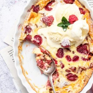 Rhubarb Raspberry Clafoutis overhead shot with ice cream and some scooped out.
