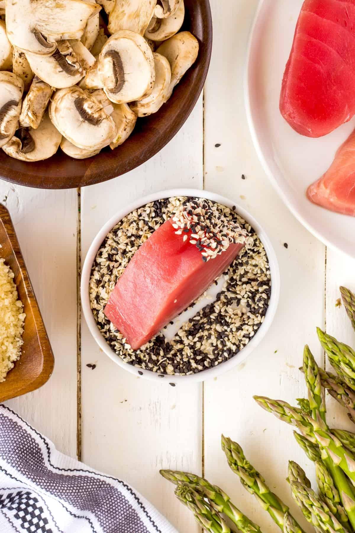 Rolling a tuna steak in sesame seeds