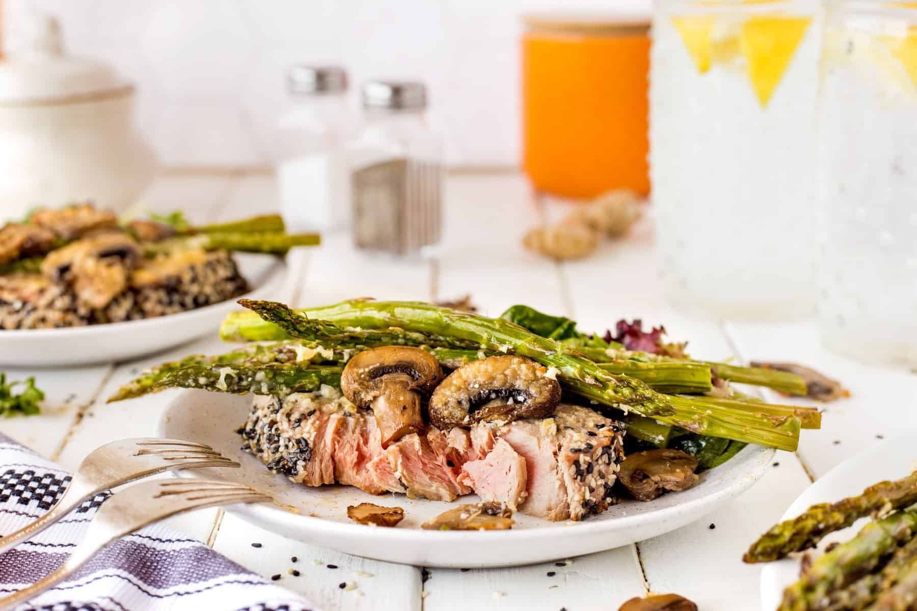 Horizontal shot of tuna steak with mushrooms and asparagus on a plate