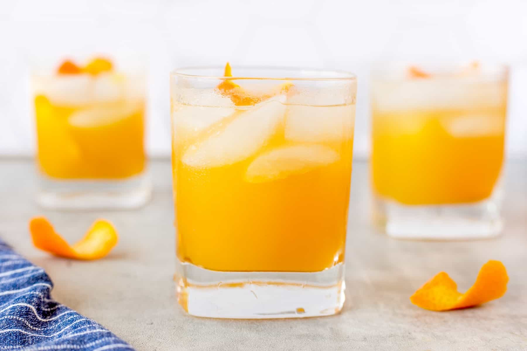 Three orange cocktails, one forward.
