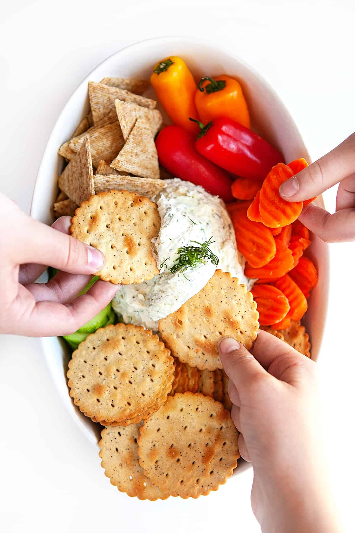 Everyone diving into a Boursin Cheese Recipe with crackers and veggies