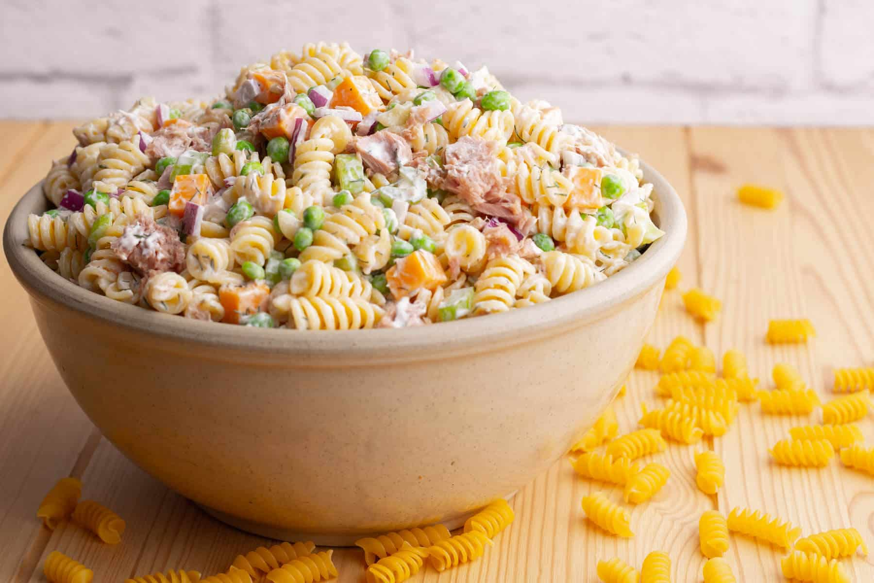 A serving bowl filled with rotini pasta, peas, tuna chunks, red onions, orange cheddar, and celery.