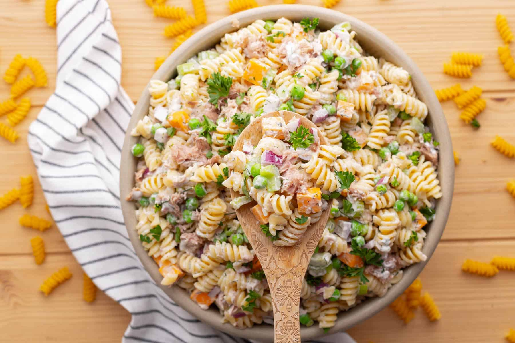 A wooden spoon holds tuna pasta salad above a bowl filled with the same salad.
