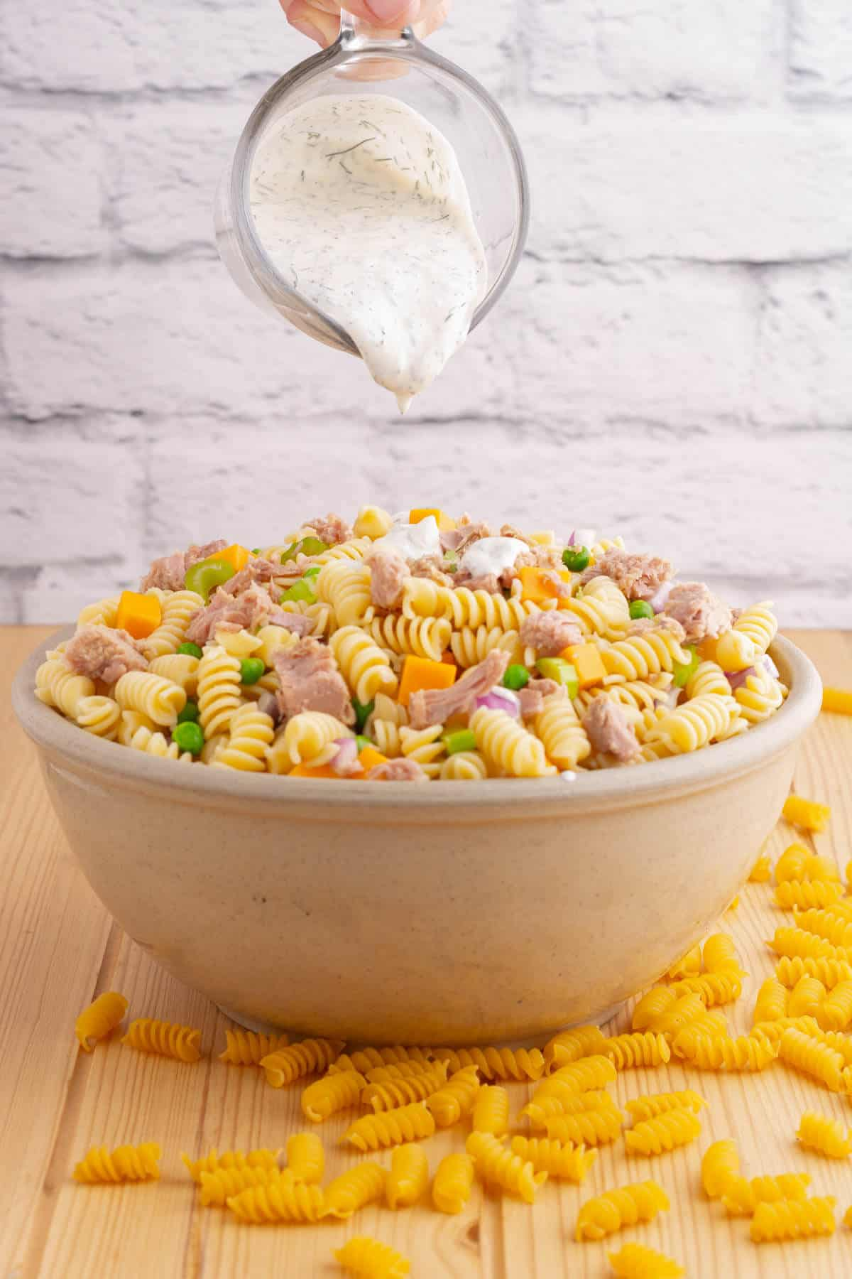 A creamy dressing being poured over a bowl of tuna pasta salad ingredients.