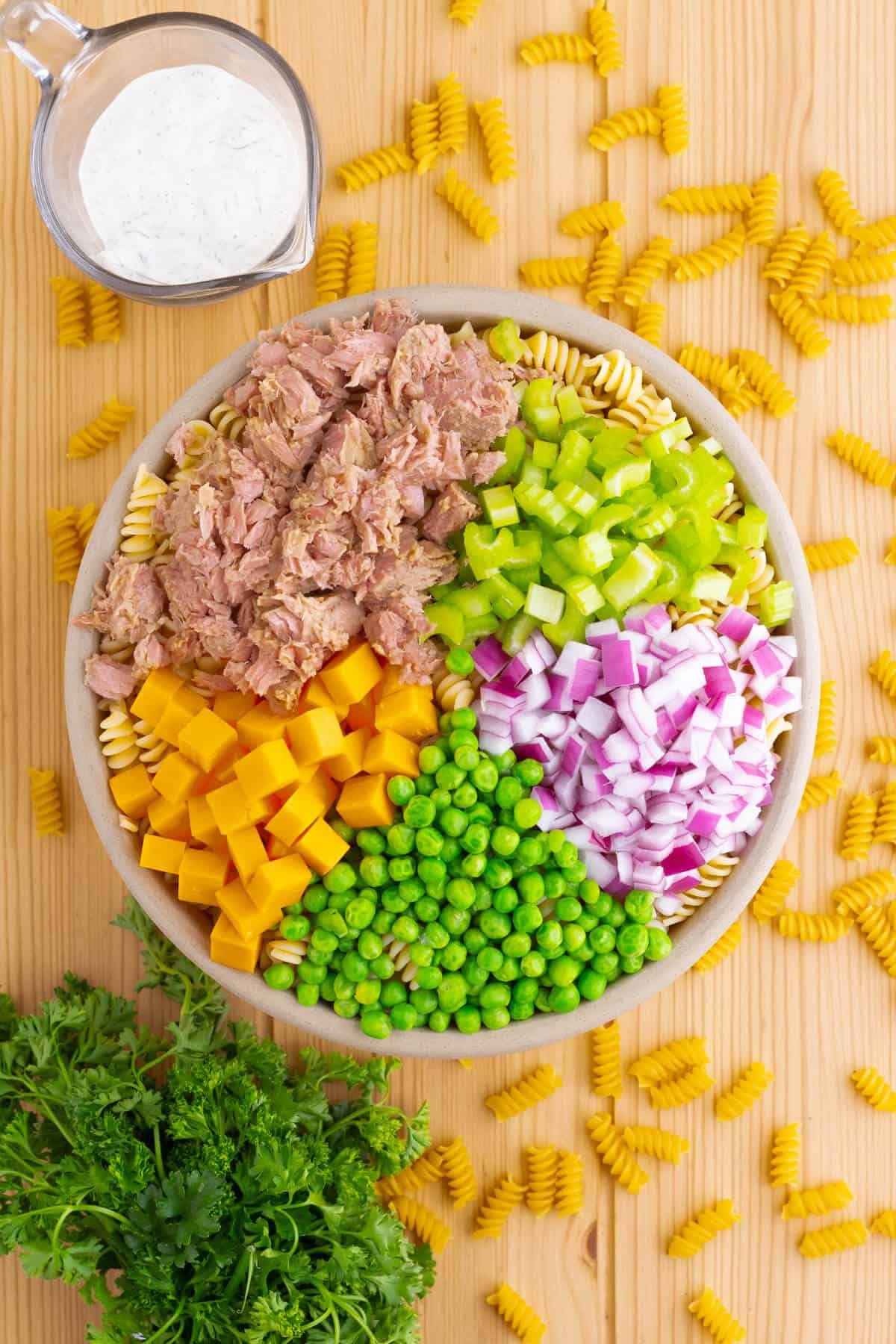 A bowl with tuna pasta salad ingredients divided into sections.