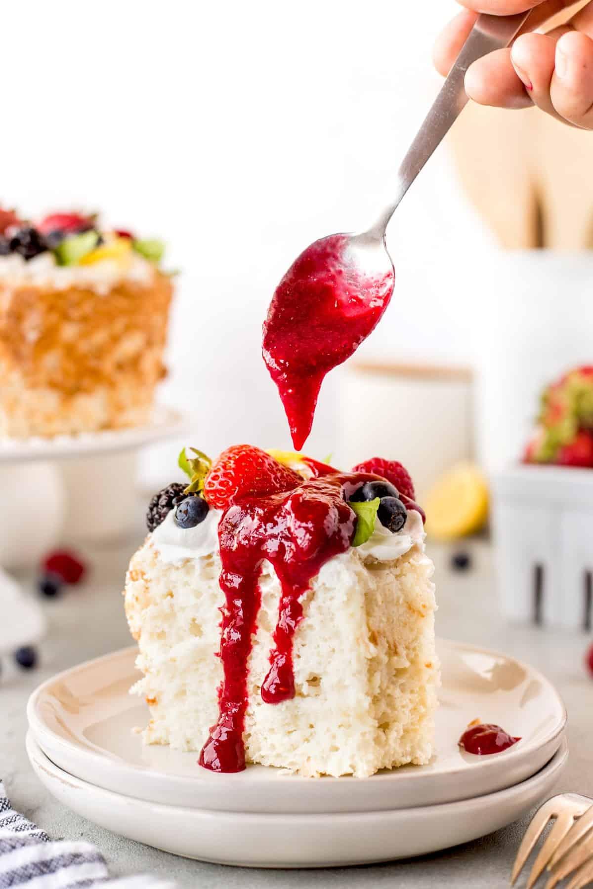 Spooning raspberry sauce onto cake