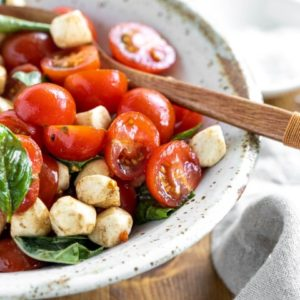 Bowl of caprese salad with a wooden spoon