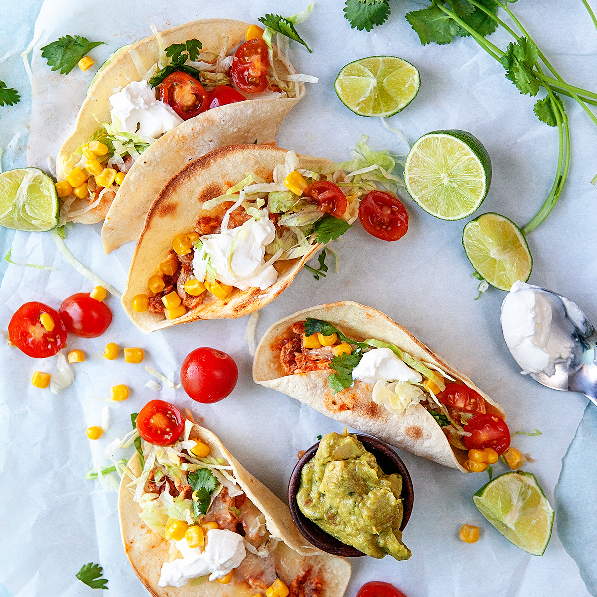 Overhead shot of tacos and toppings on parchment paper