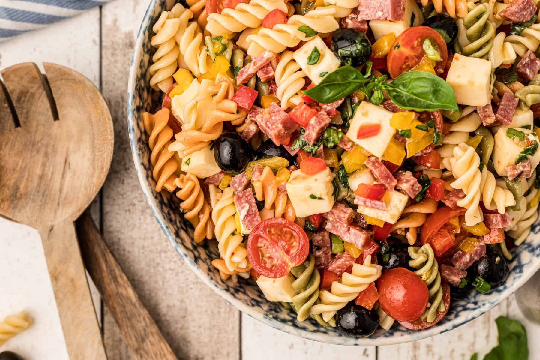 Overhead Italian pasta salad with wooden salad servers.