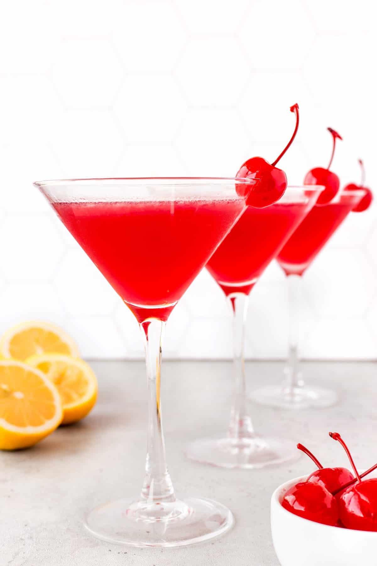 Three Lemon Cherry Martinis lined up garnished with maraschino cherries.