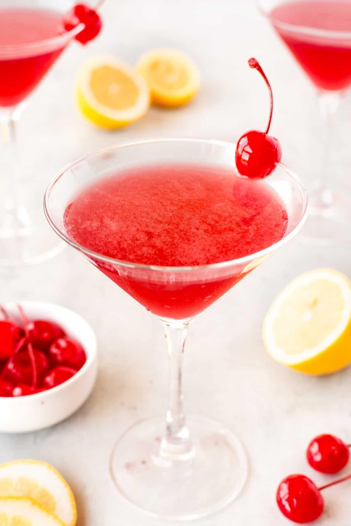 Showing one martini with maraschino cherries and lemon slices