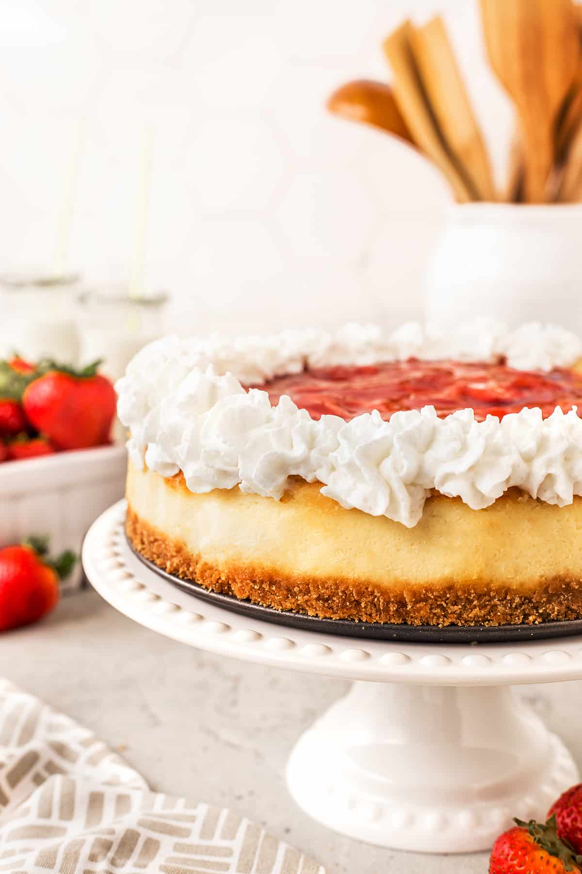 Finished Light and Airy Strawberry Cheesecake on a cake stand