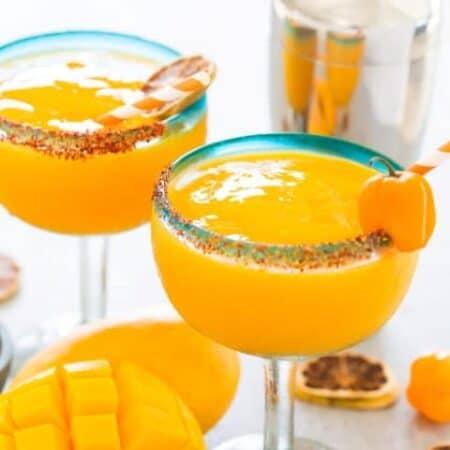 Mango Habanero Margaritas in glasses, shaker and fresh mango.