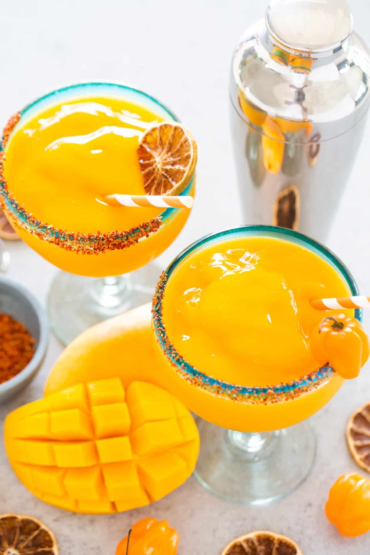 Two margaritas with garnish and cocktail shaker, also fresh cubed mango.