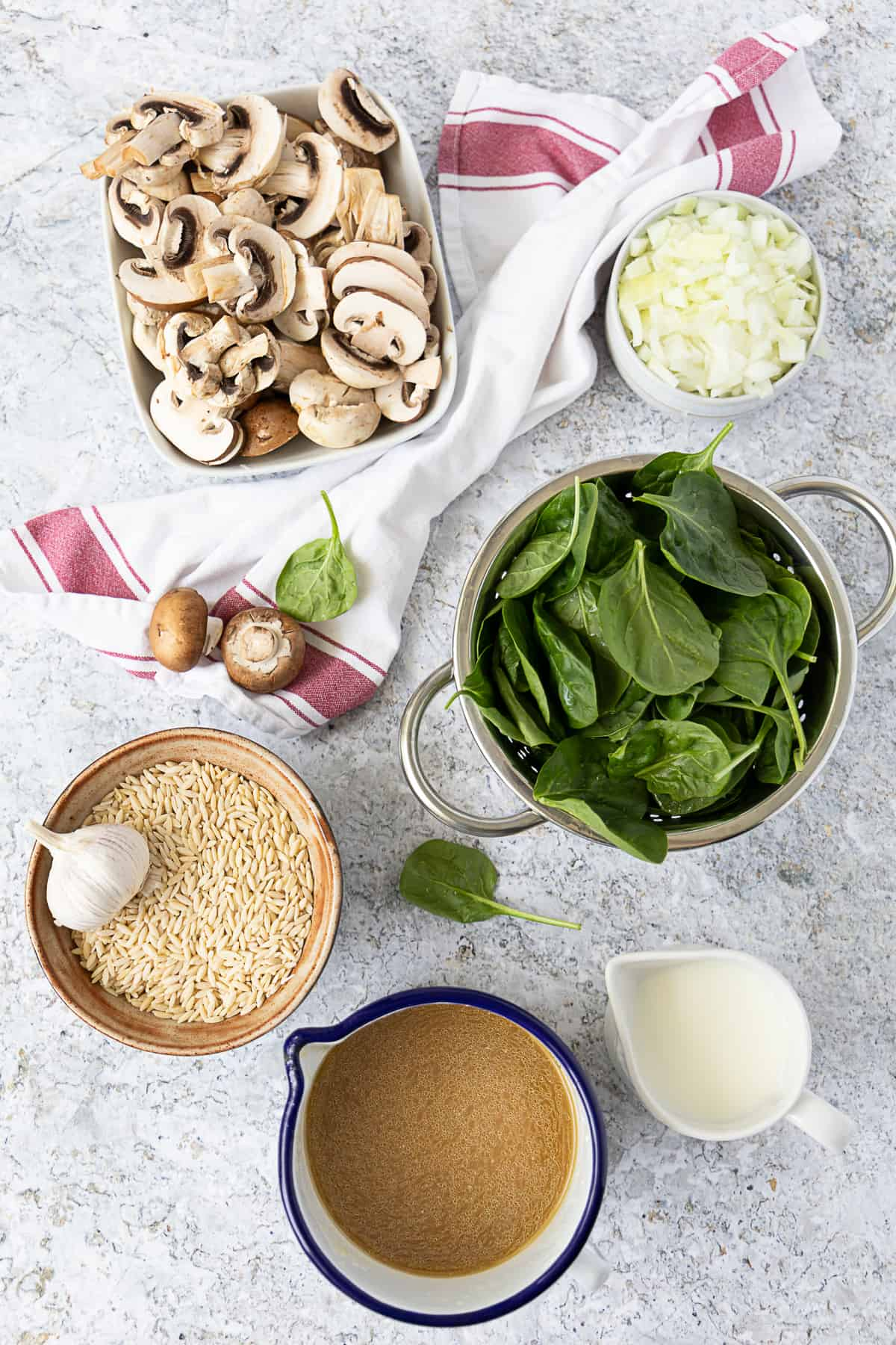 top view of ingredients for mushroom orzo: orzo, mushrooms, spinach, onion and garlic.