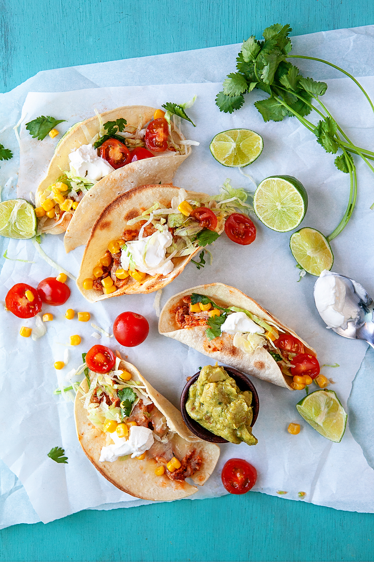 Overhead of tacos and toppings on parchment