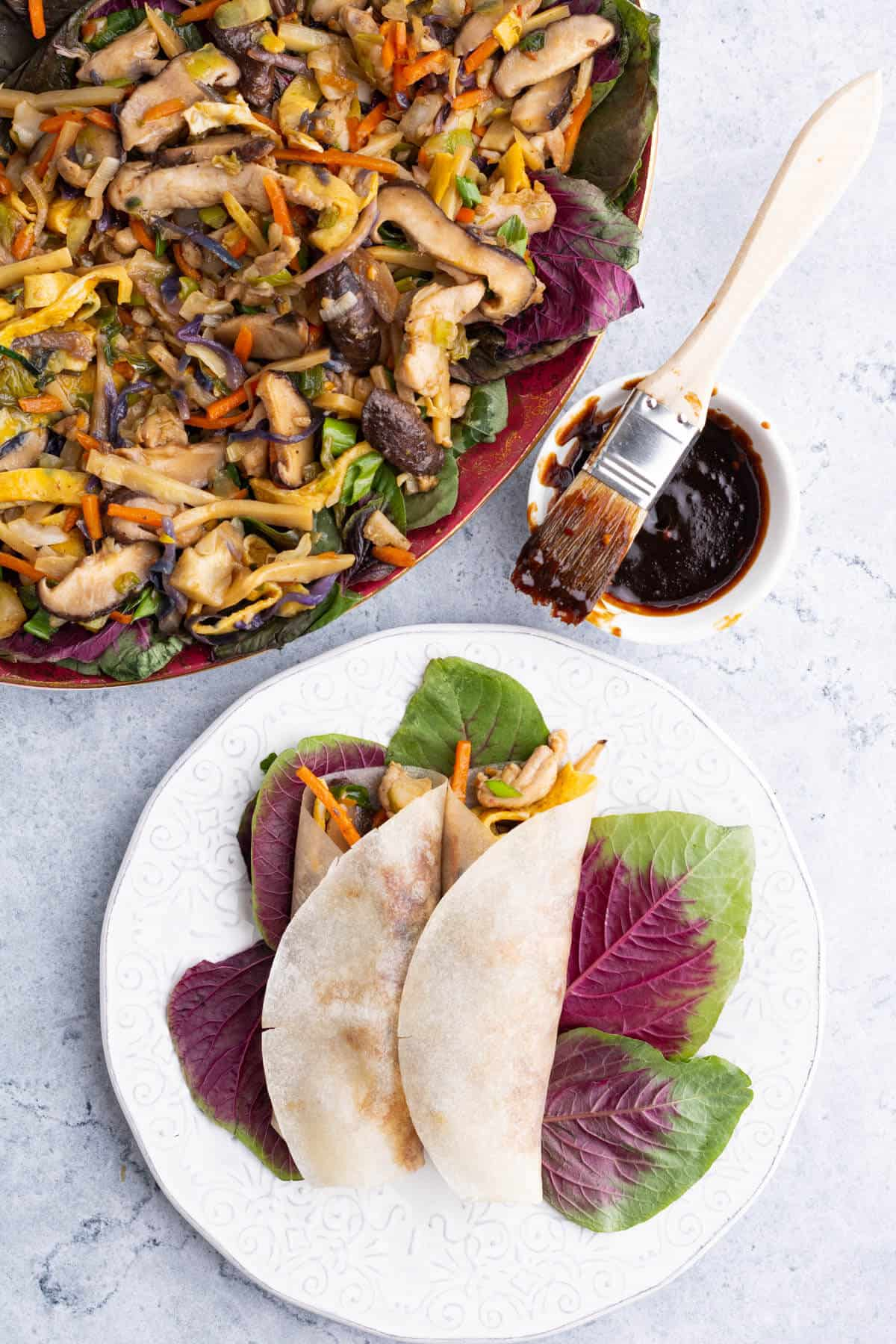 A platter full of colourful Moo Shu Chicken and two filled and rolled pancakes.