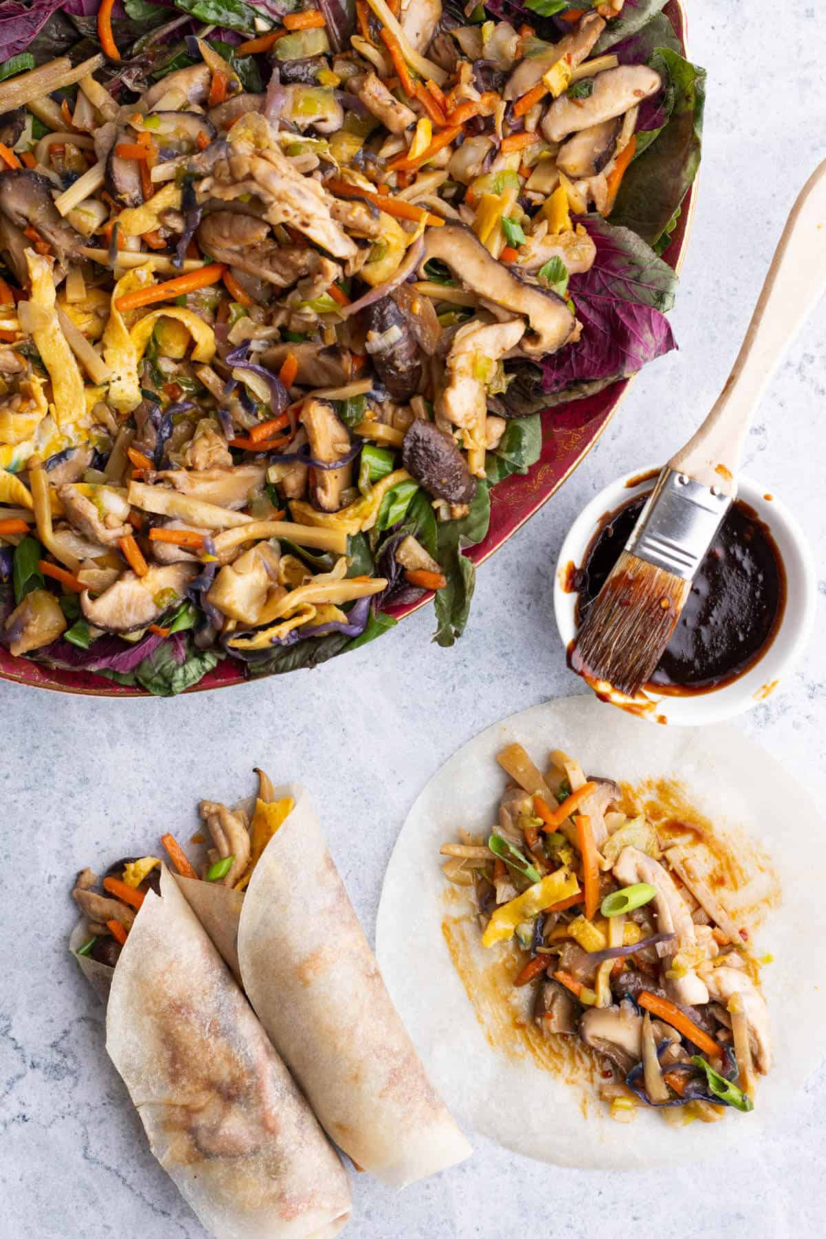 A platter full of colourful Moo Shu Chicken beside two rolled pancakes.