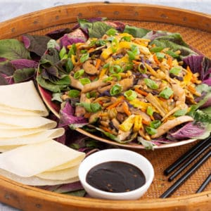 A platter full of colourful Moo Shu Chicken with Chinese pancakes and a dish of hoisin sauce.
