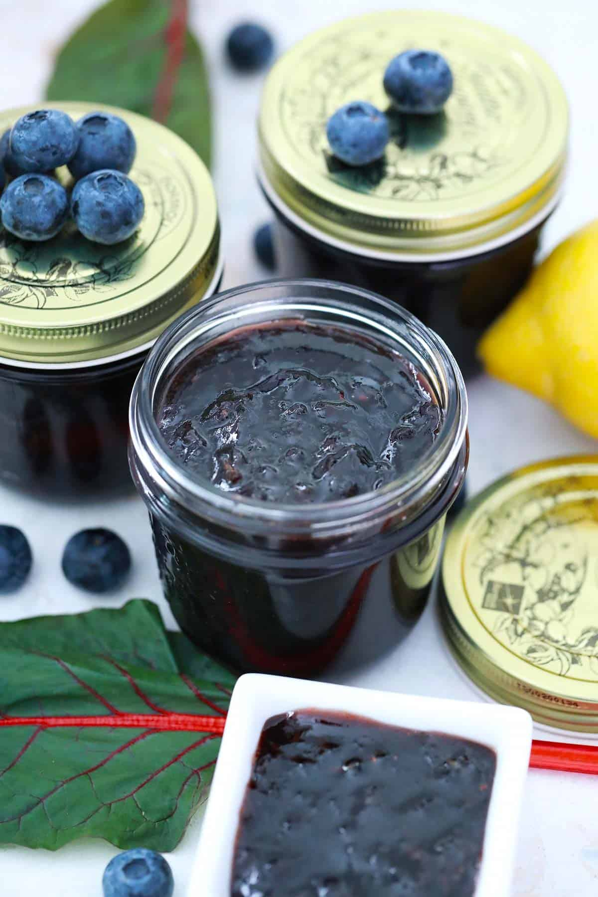 Jars of jam, one opened others with lids and blueberries on top