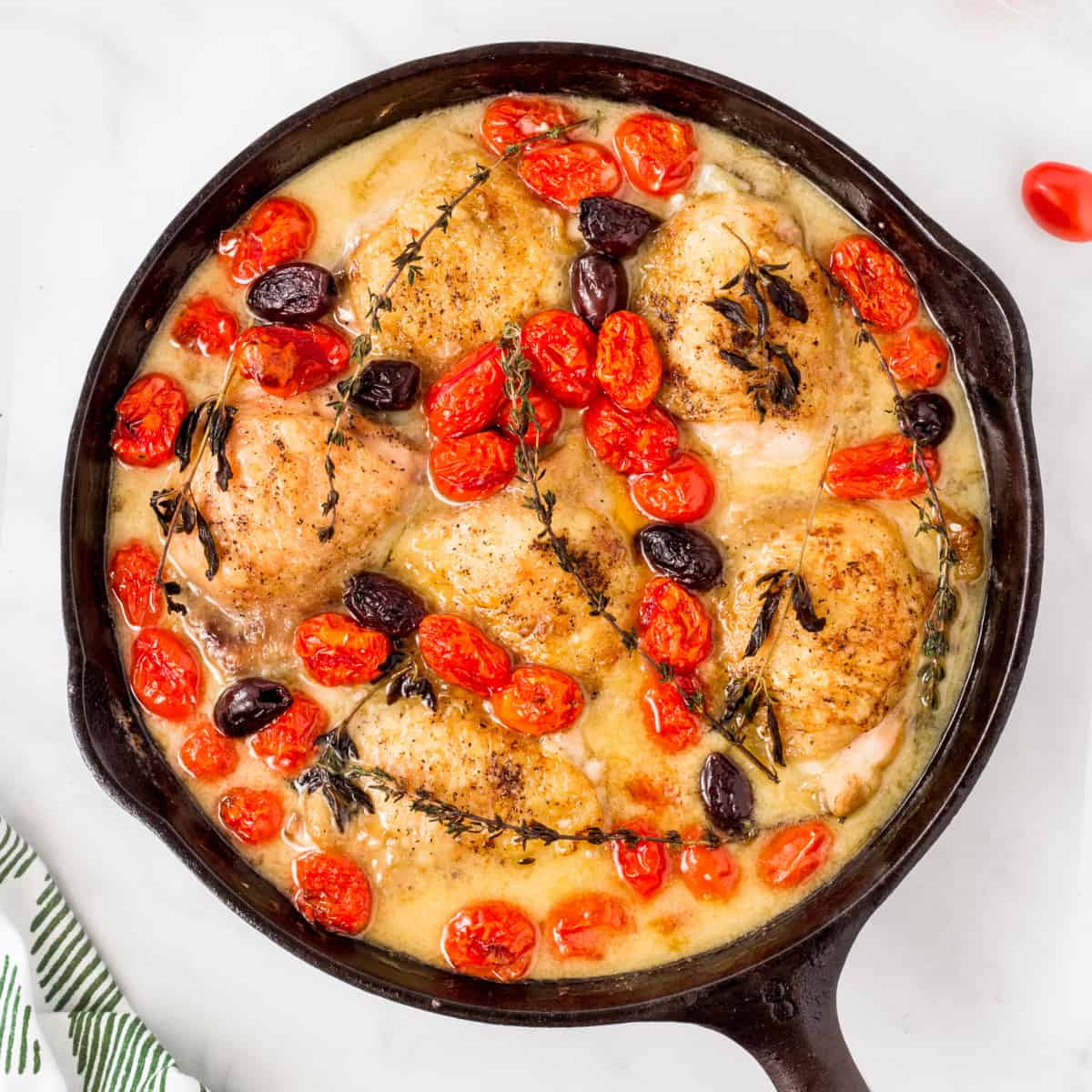 Overhead square photo of chicken dinner with olives and tomatoes
