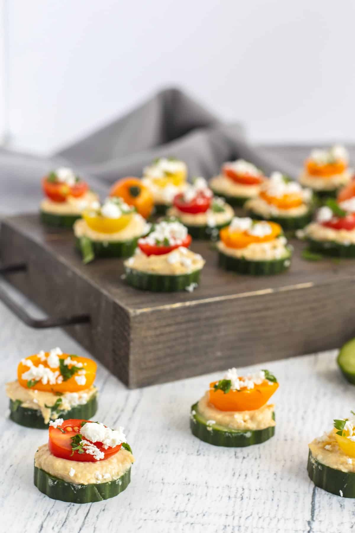 Cucumber Hummus Bites on a wooden board and table top