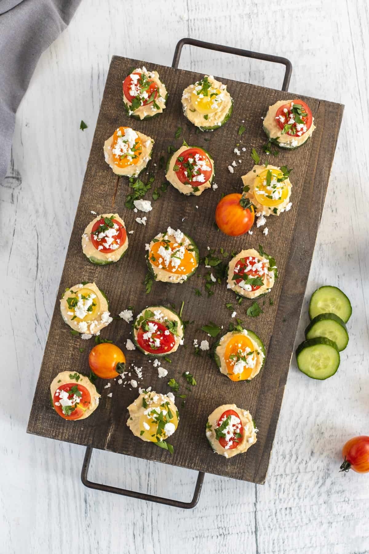 Overhead shot of Cucumber Hummus Bites on a wooden serving board