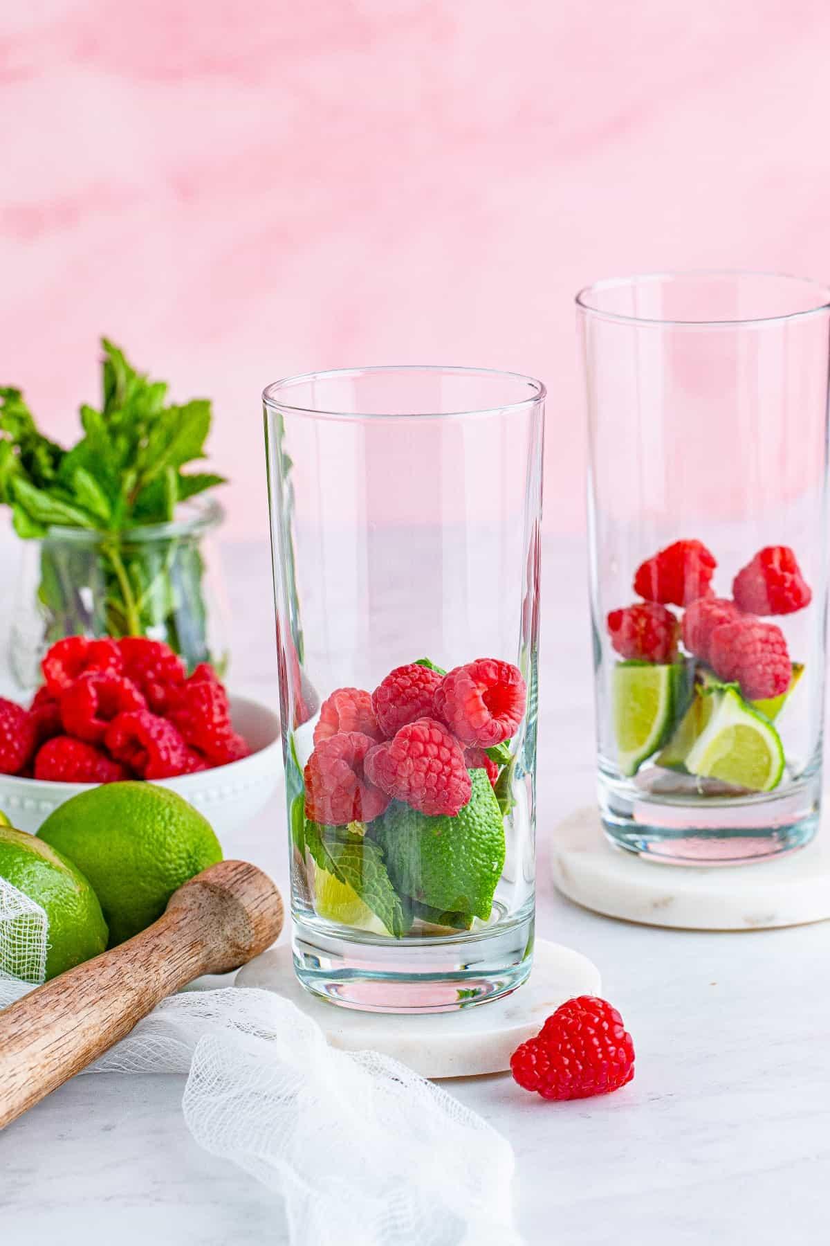 Raspberries, limes and mint in a glass.