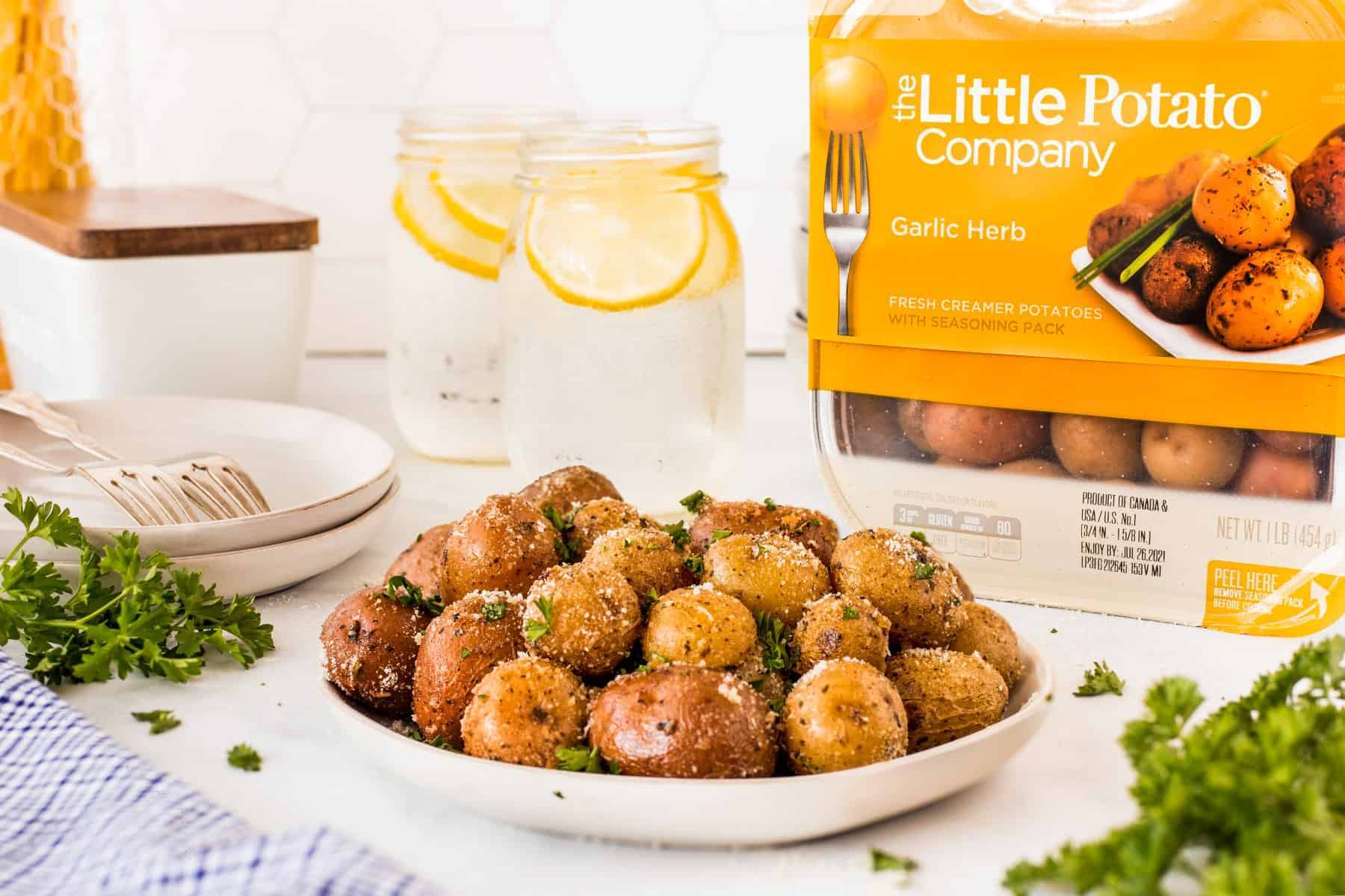 Potatoes on a plate with a package of potatoes behind from Little Potato Company.