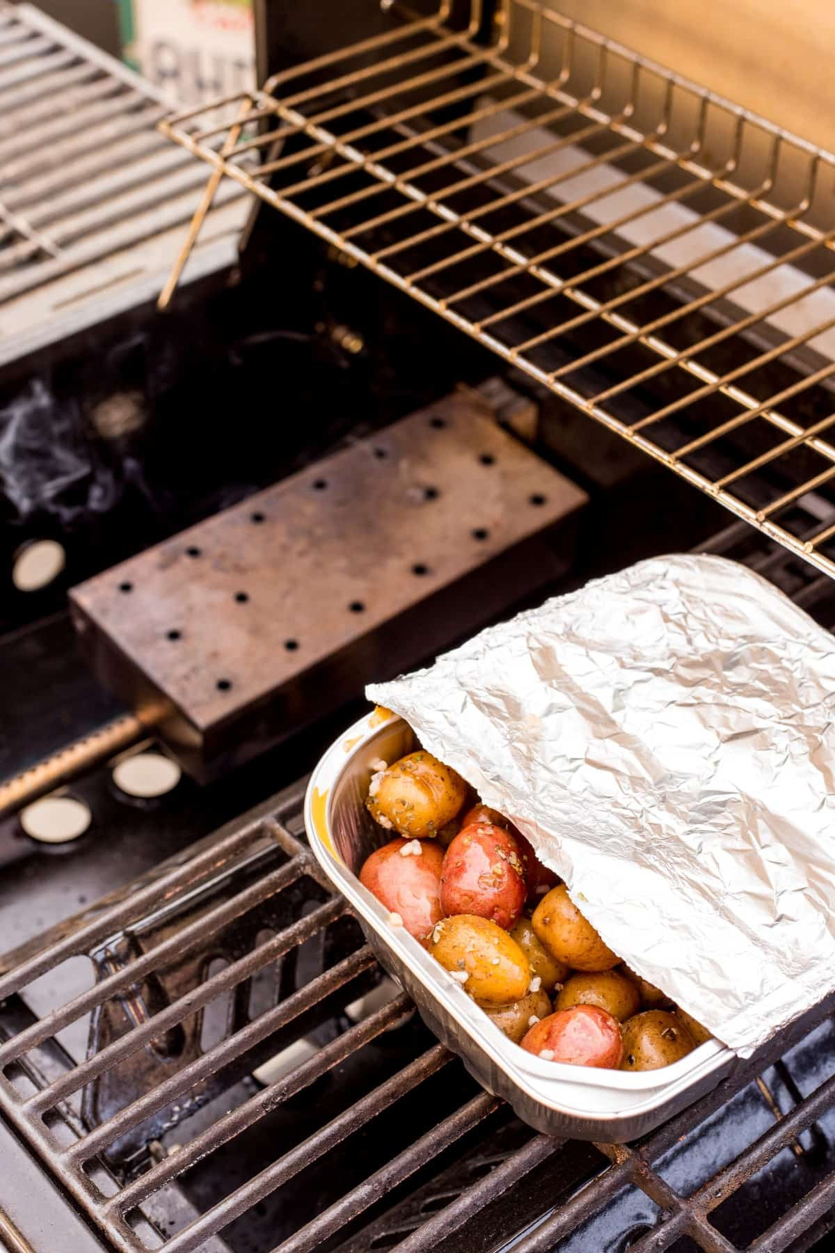 Potatoes in a pan partially covered in foil on the grill.