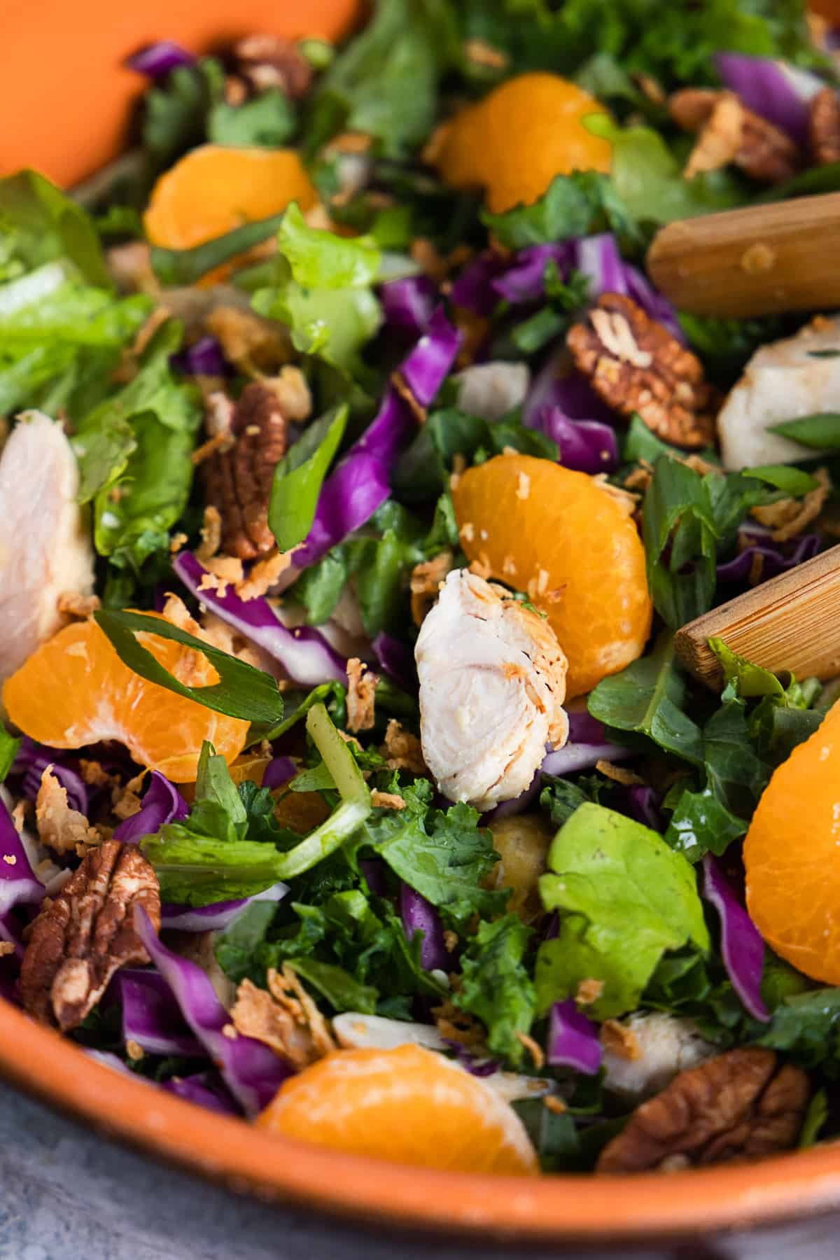 Close up of the salad featuring mandarin, chicken, red cabbage, lettuce and kale