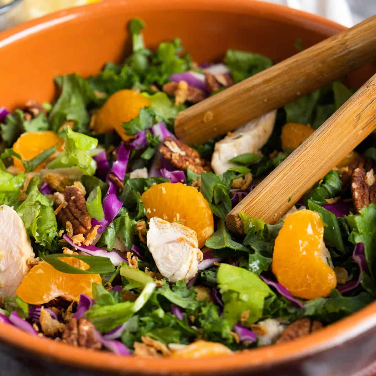 Mandarin Chicken Salad in a wooden bowl with tongs.