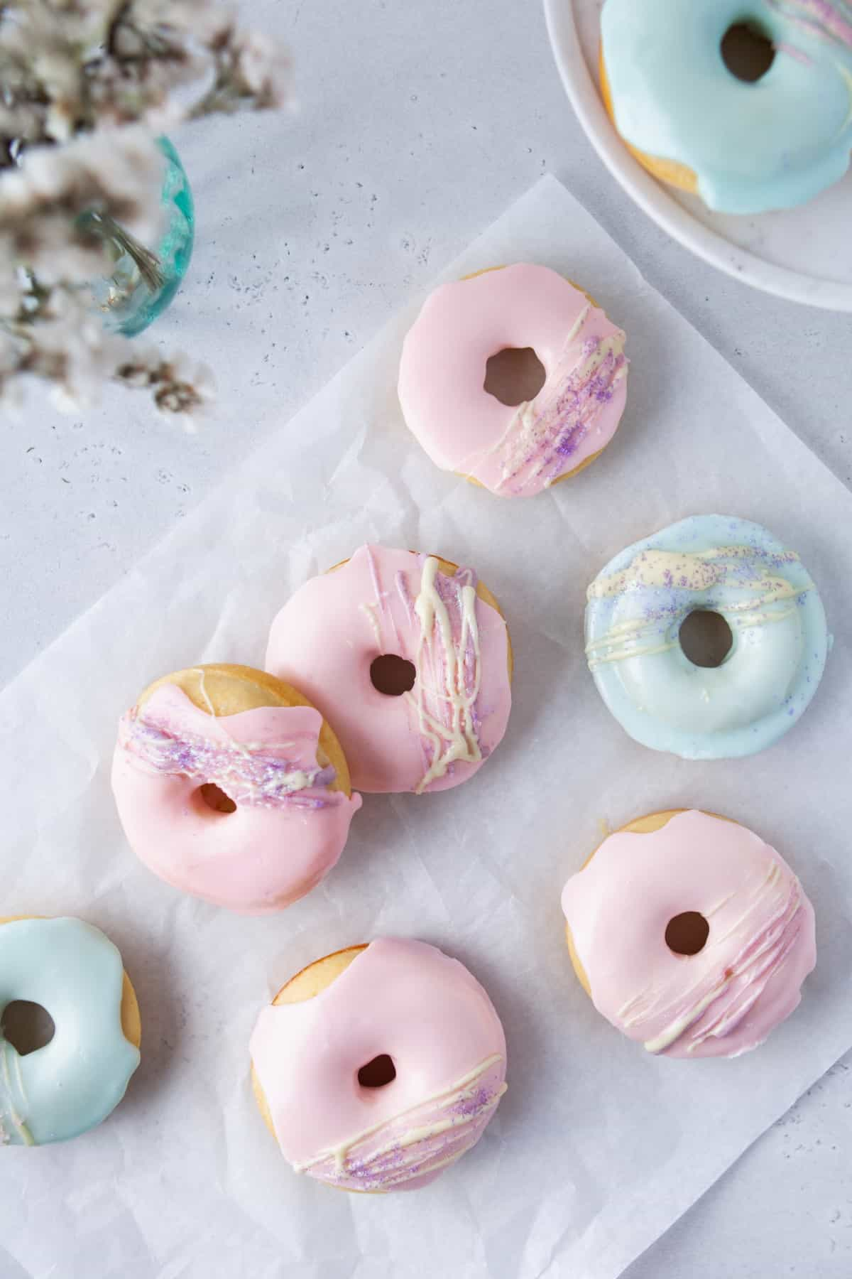 Overhead Vanilla Baked Buttermilk Donuts decorated with pink and blue icing.