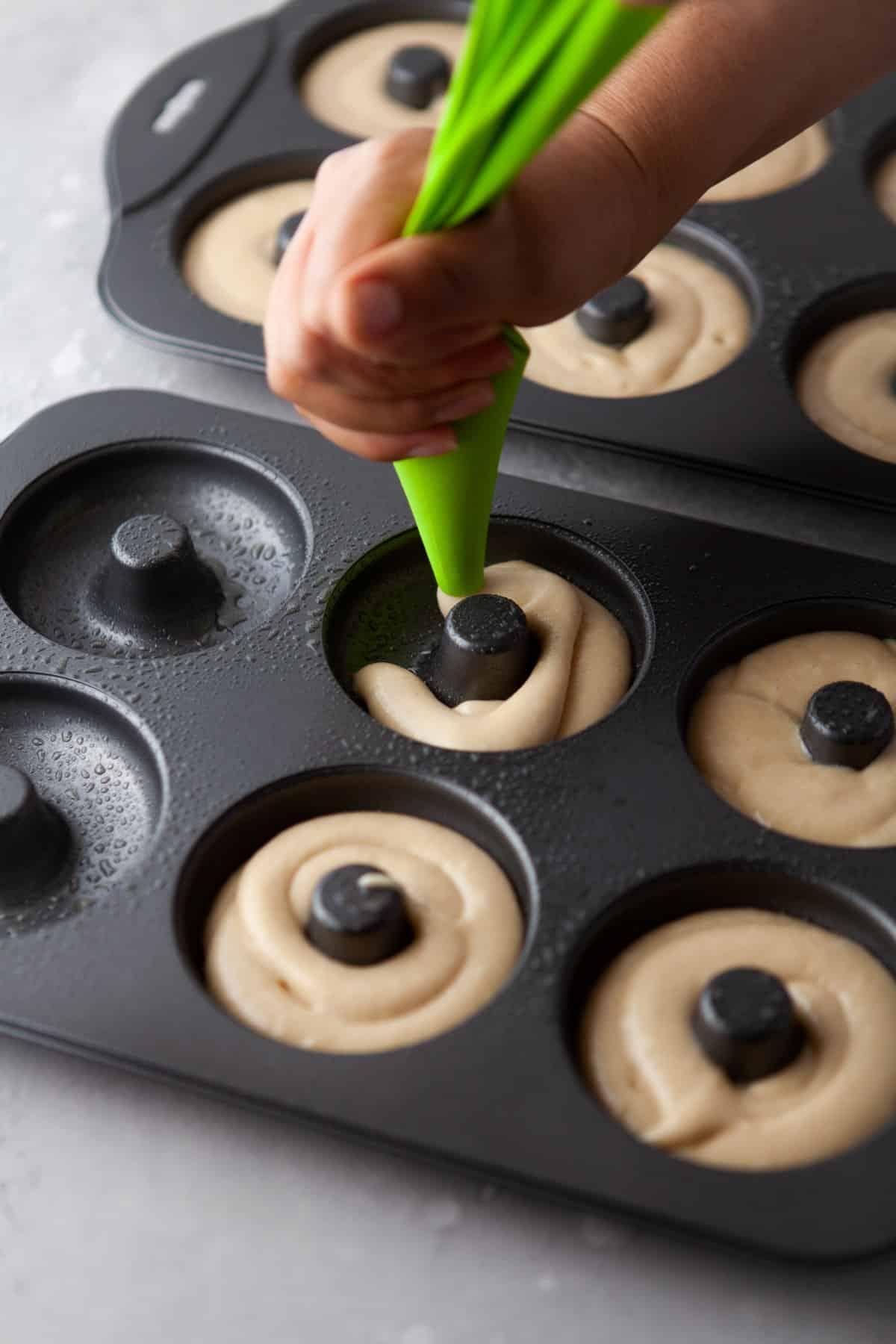 Piping batter into a donut pan