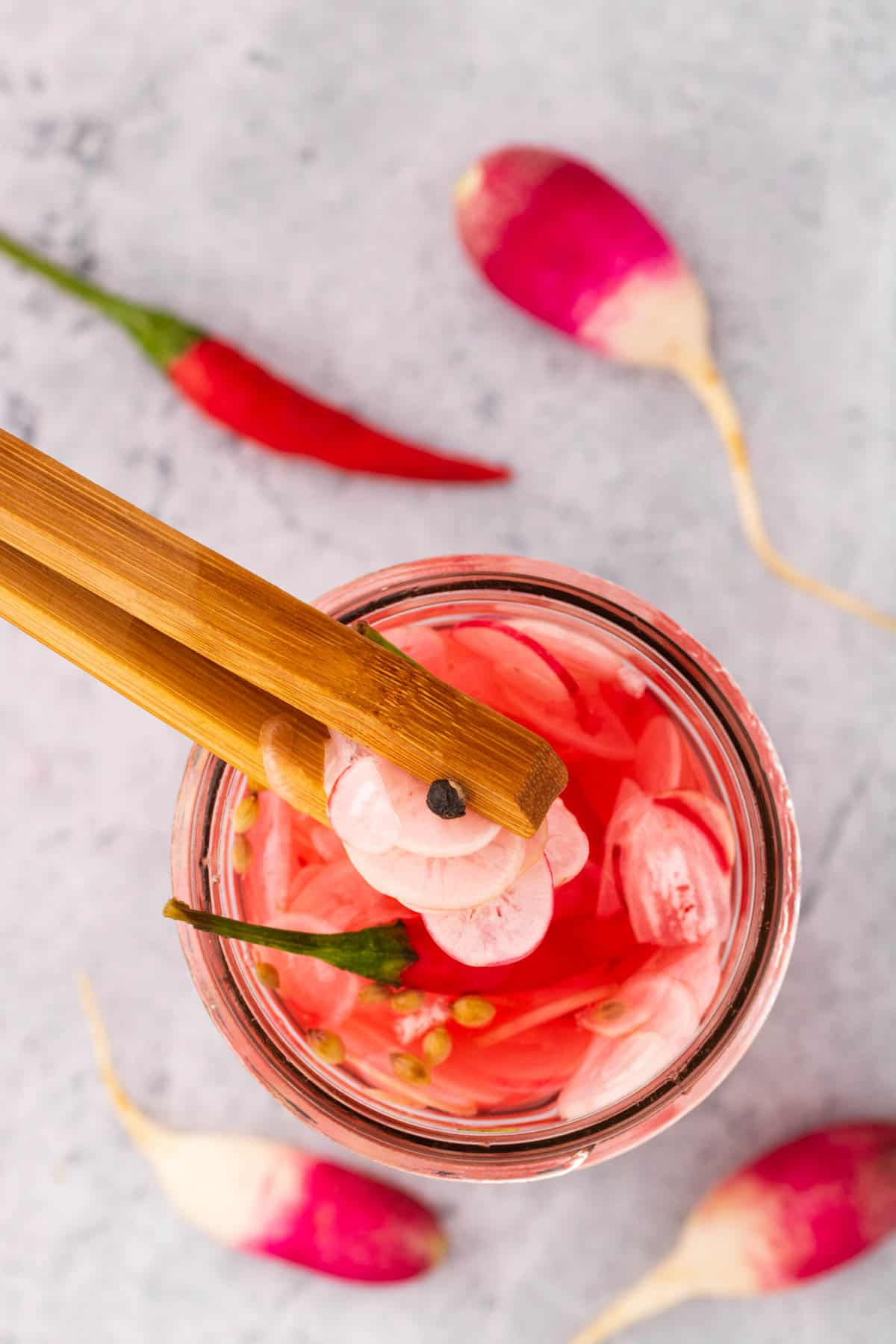 A pair of wooden tongs grabbing quick pickled radishes out of a jar.
