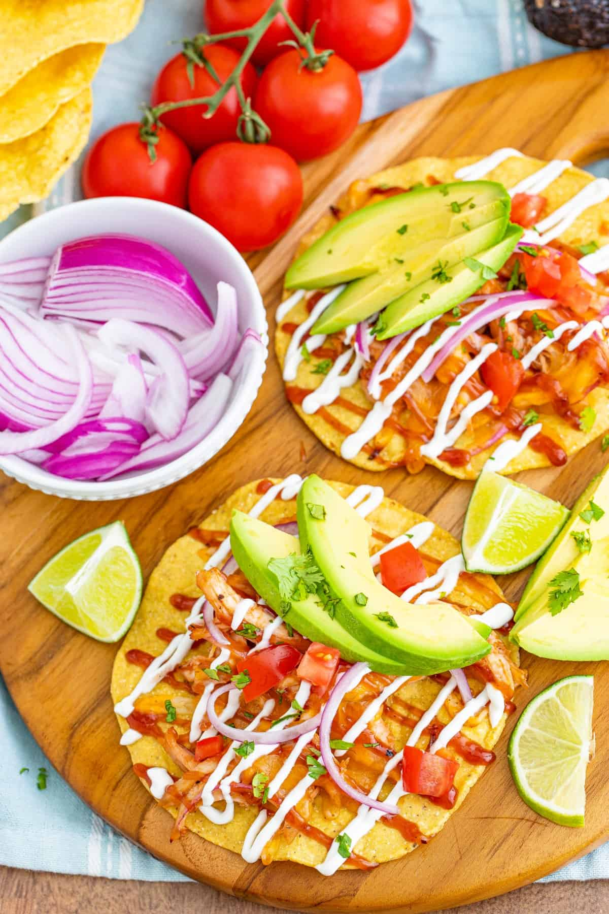 Two BBQ Chicken Tostadas with a bowl of sliced red onion, limes, and avocado.