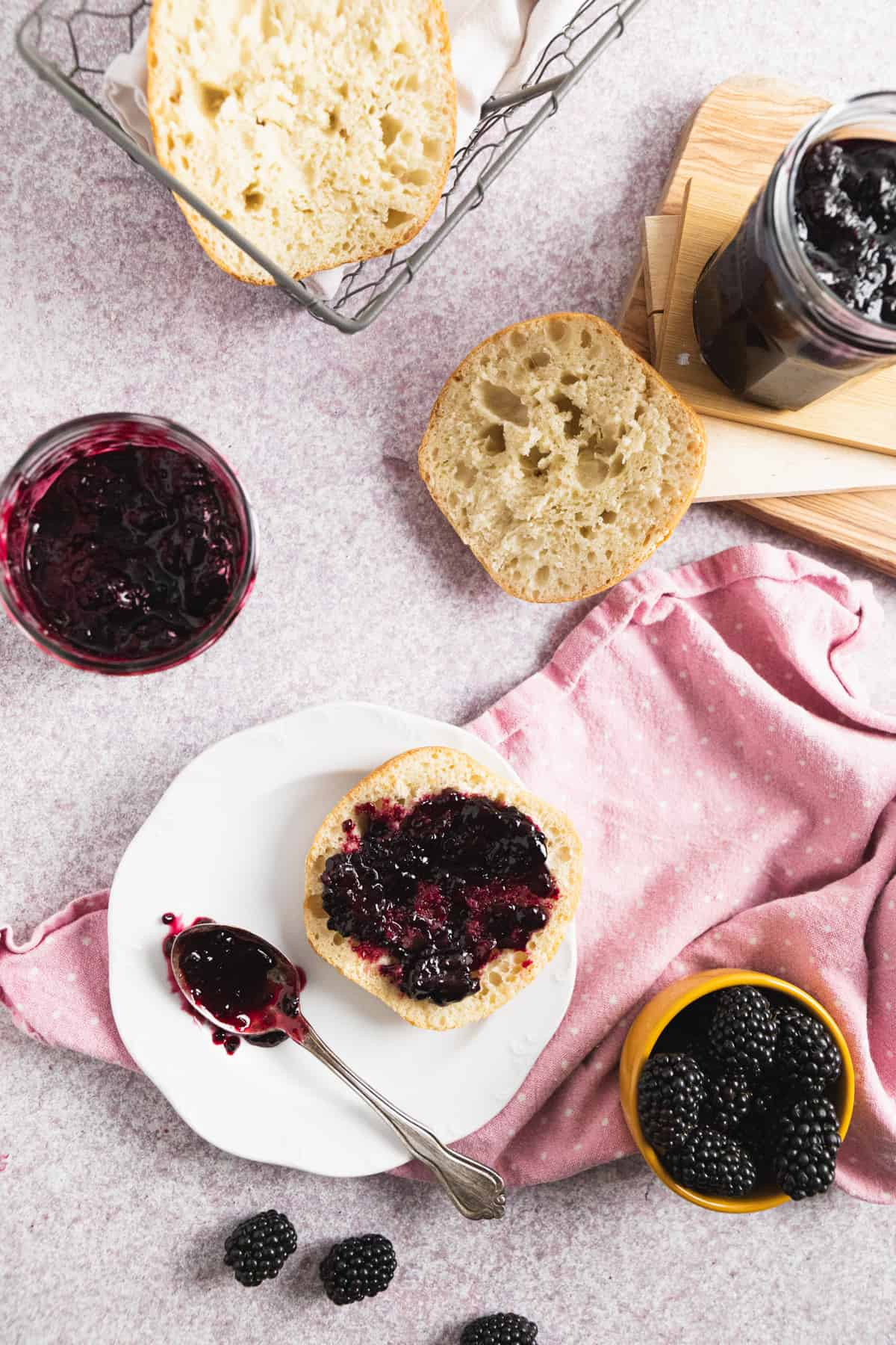 Top view of breakfast scene with bread and blackberry freezer jam on a slice of bread on a plate.