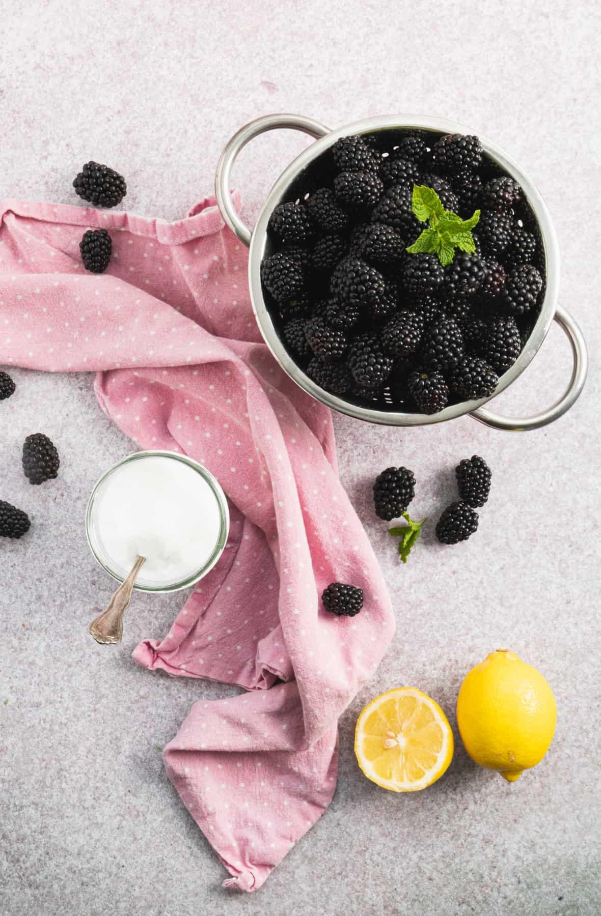 Top view of the ingredients to make jam, fresh blackberries in a colander, sugar and lemon.