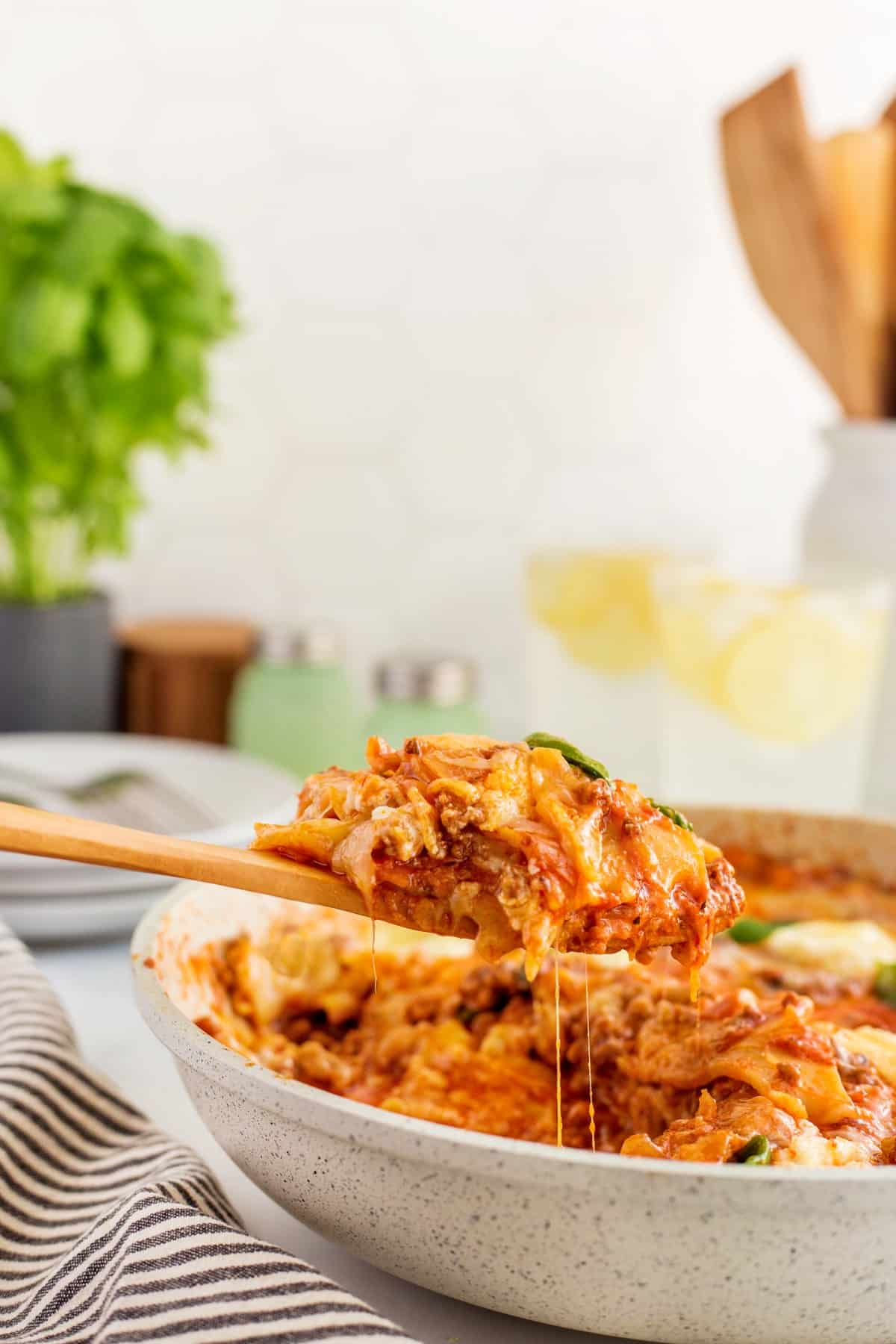 Scooping out skillet lasagna with a wooden sppon.