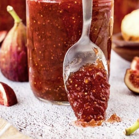 Fig jam on a spoon resting up against a jar of fig jam