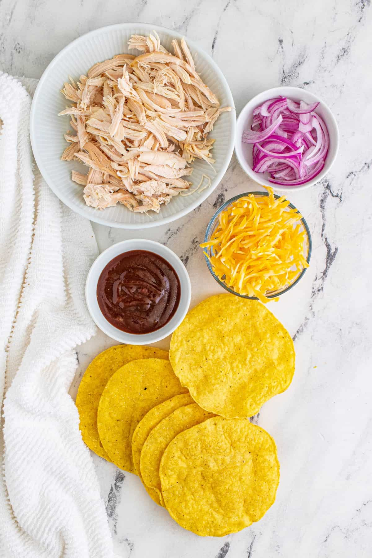 Ingredients for BBQ chicken tostadas in separate bowls on a marble surface.