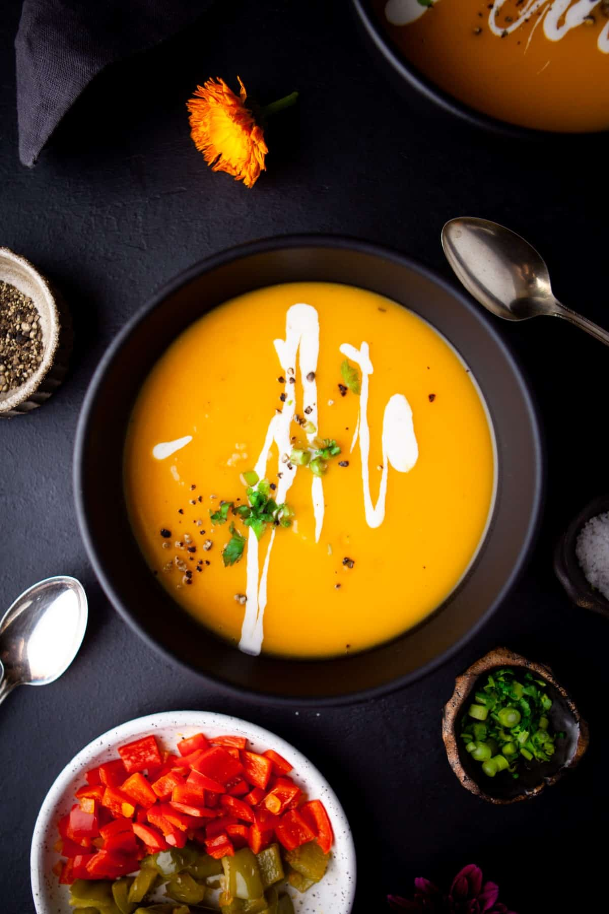 Overhead of Butternut Squash Soup in a black bowl with sour cream drizzle and cilantro