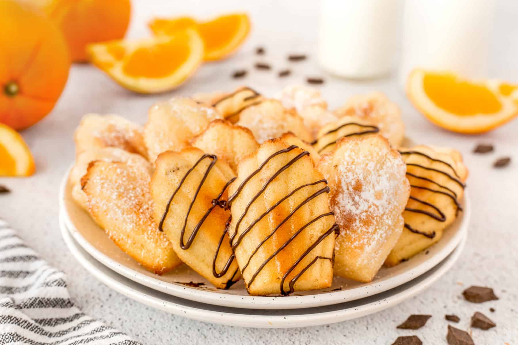 Horizontal shot of madeleines on a plate with sliced oranges in the background.