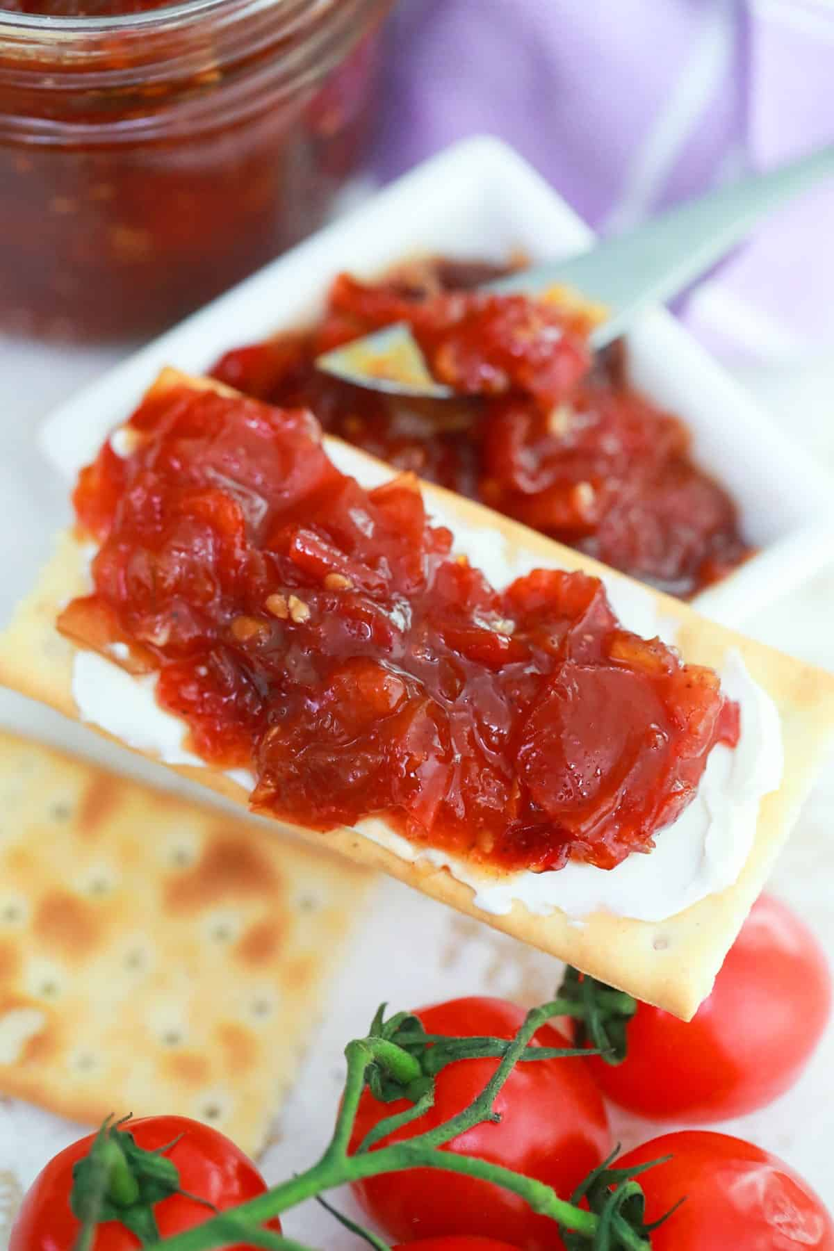 Tomato jam on a cracker with cream cheese.