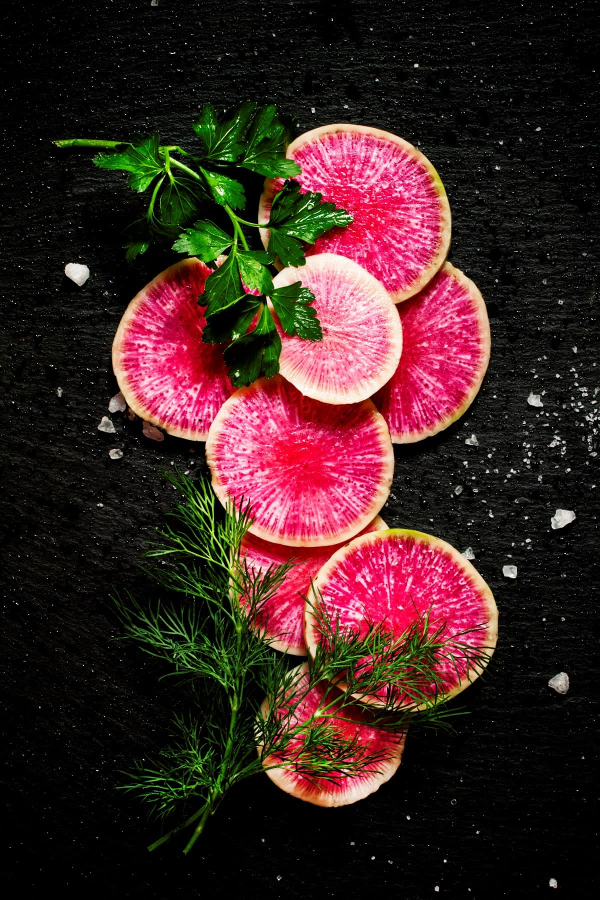 Food background: round slices of watermelon pink radish, dill, parsley, salt, black stone background, top view