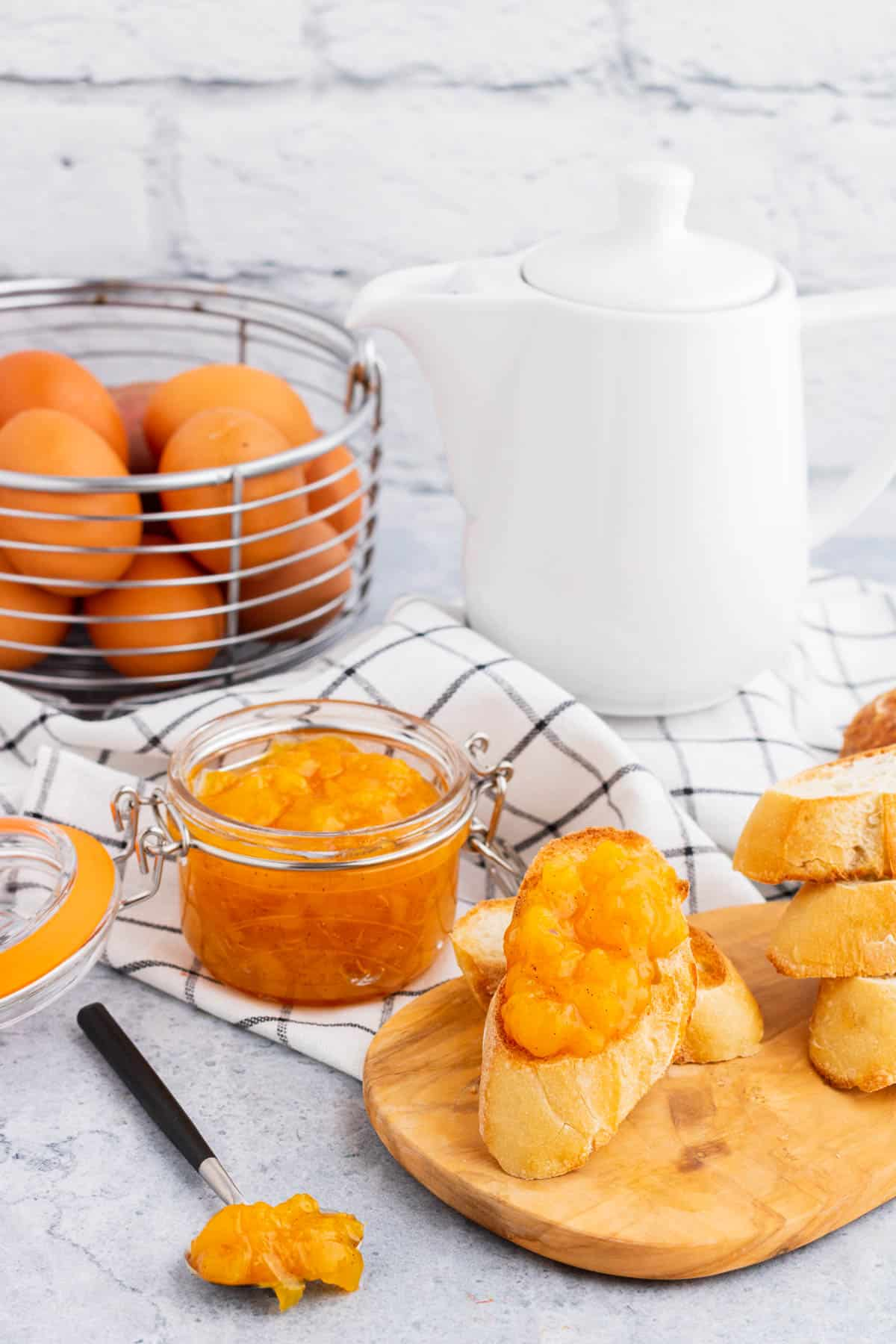 Breakfast scene with a coffee pot, eggs, and toast covered in bright orange Peach Freezer Jam in front of a jar of the same jam.